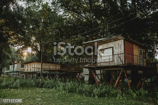 Old elevated battered weekend houses standing under the trees in hungarian campsite in city of Szeged, during the sunny summer daybreak with the sun shining through the trees