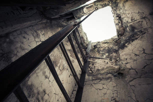 Old empty abandoned bunker interior Old empty abandoned bunker interior with rusted metal ladder going up to glowing manhole bomb shelter stock pictures, royalty-free photos & images