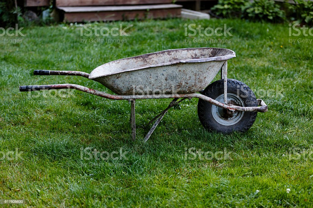 Old empty and dirty metal wheelbarrow on grass stock photo