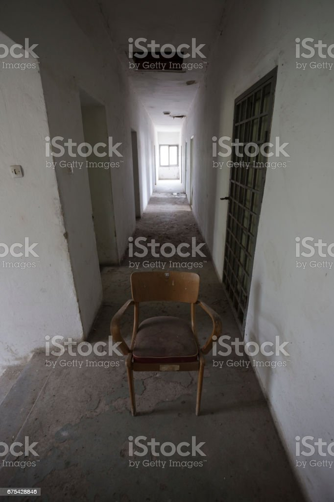 Old empty chair in abandoned building hallway royalty-free stock photo