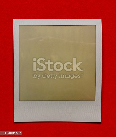 1183352589 istock photo old empty instant film frame on real paper background 1145594327