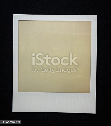 1183352589 istock photo old empty instant film frame on real paper background 1145594329