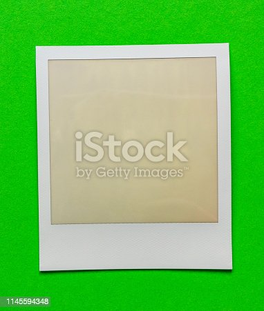 1183352589 istock photo old empty instant film frame on real paper background 1145594348