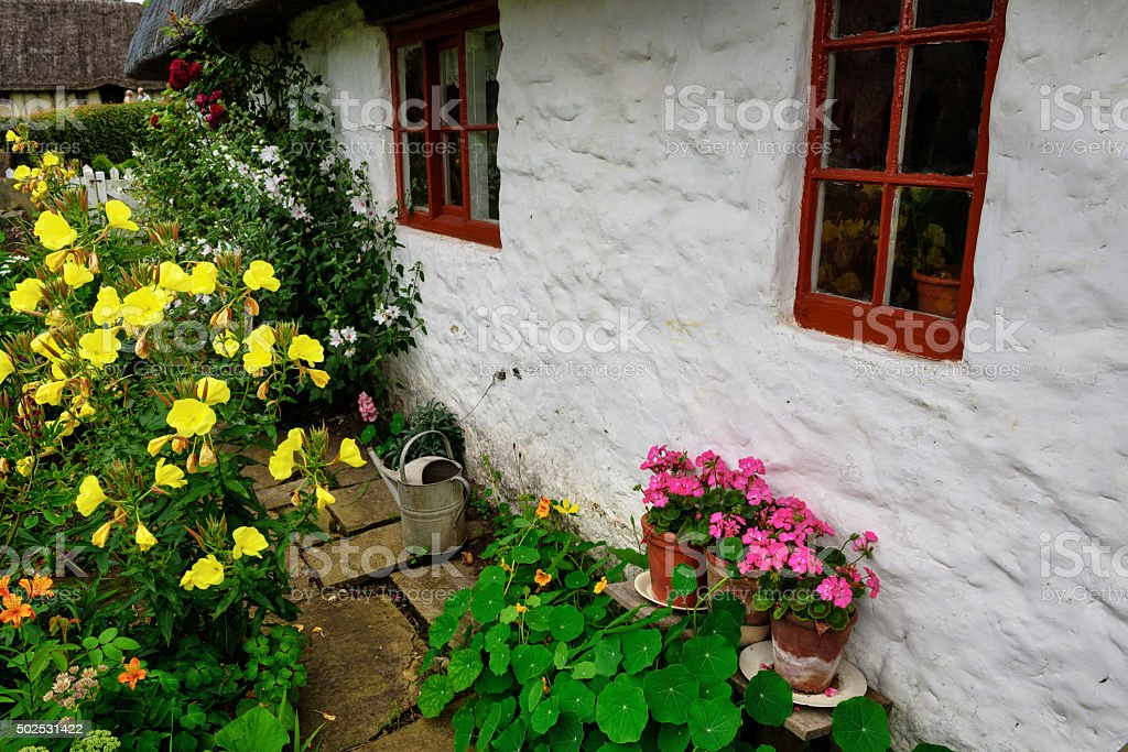 Old English cottage garden with watering can stock photo