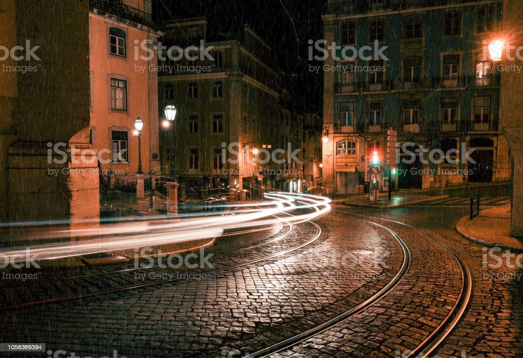 Old European city street at rainy night, Lisbon, Portugal
