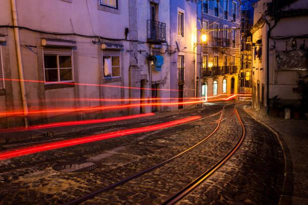 old european street at night. lisbon, portugal - linea tranviaria foto e immagini stock