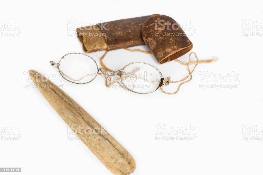 Old eyeglasses with paper case and ivory tab on white background stock photo