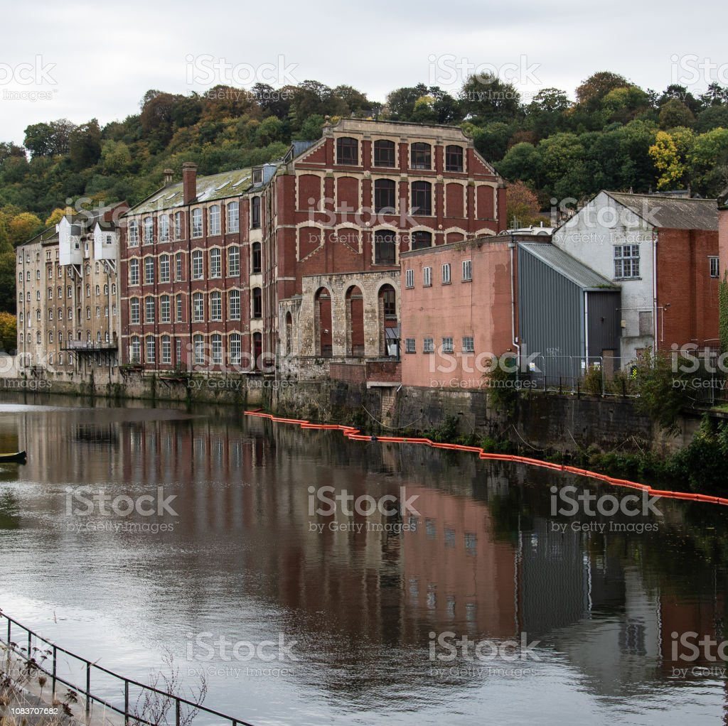Old factories adn warehouses reflected in the water of the River Avon stock photo