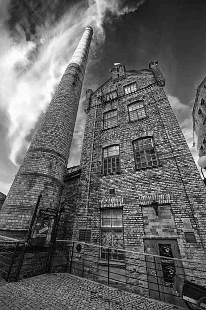 Old factory chimney in the industrial landscape of Norrkoping. stock photo