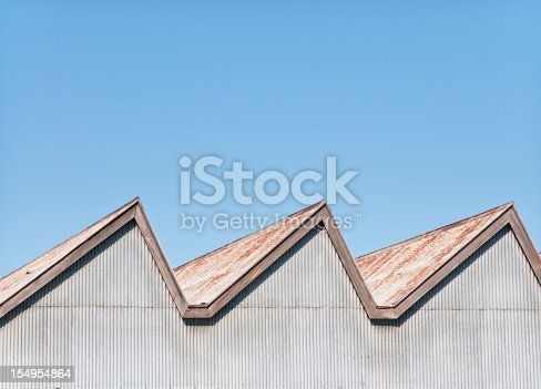 Abstract close-up image showing the rusting corrugated iron roof and top walls of an old and run down, traditional factory building.