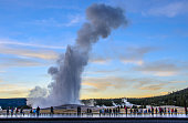 Groups of people have been waiting to watch, experience and photograph this Old Faithful  eruption just after sunset on a sunny early autumn day.