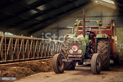 Shot of a rusty old tractor standing in an empty barn