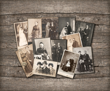Old family photos laid out on wooden background