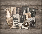 group of vintage family and wedding photos circa 1890-1920. nostalgic sentimental pictures on rustic wooden background