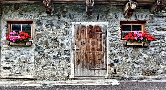 Old farm house made of field stones with wooden door, two windows and bright red flowers
