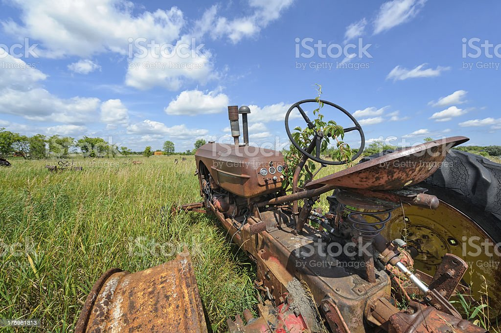 Old Farm Tractor in Junkyard Field and Summer High Grass royalty-free stock photo