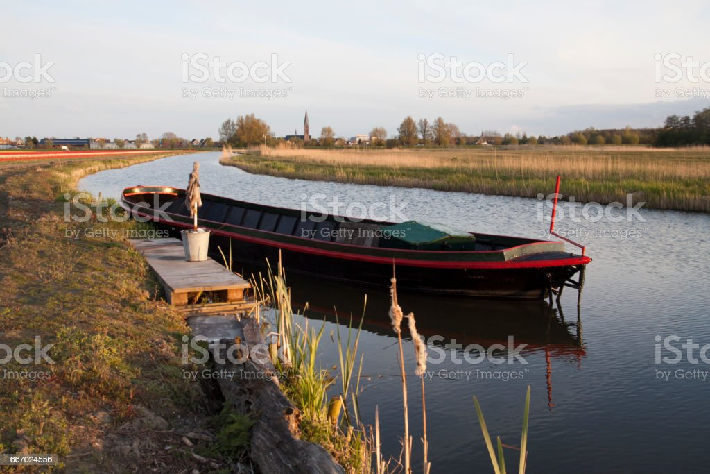 Old farm transport boat in the water stock photo