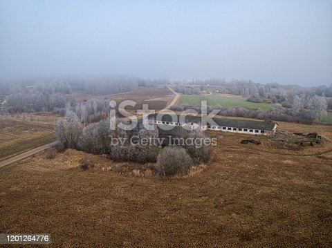 Abandoned and destruction livestock farm. Aerial view, mystical landscape view  in the morning fog.