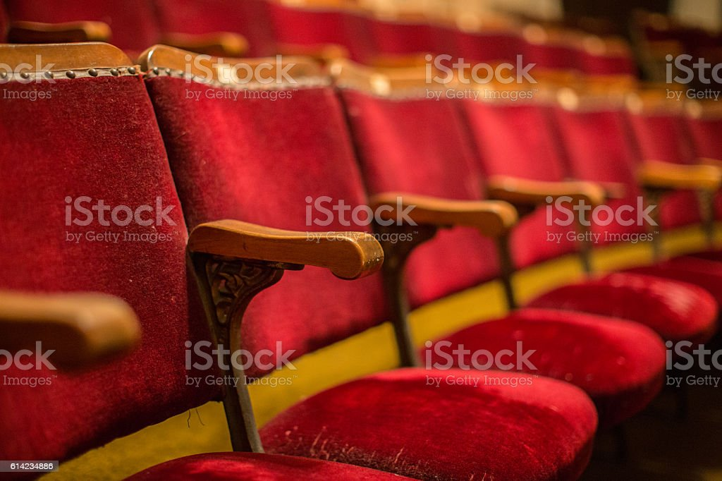 Old fashion cinema theatre seats with wooden arms flip-up seats stock photo