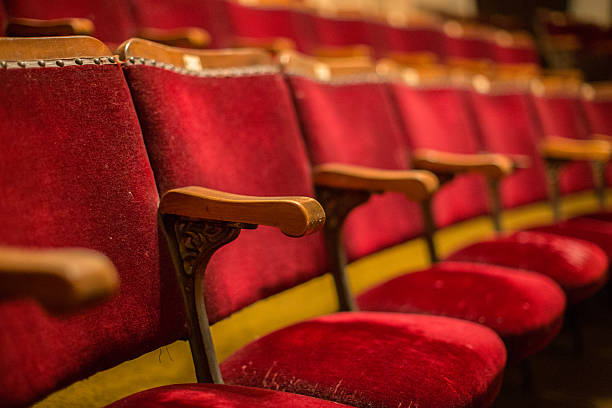 Old fashion cinema theatre seats with wooden arms flip-up seats - foto stock