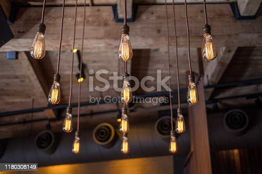 A collection of twelve old fashion style light bulbs hang neatly from the wood ceiling of this building. The exposed wooden beams are visible in the background.