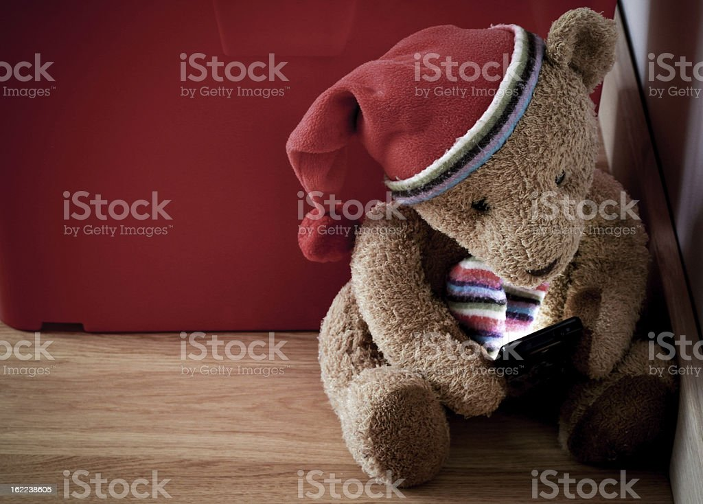 Old fashion teddy checking on a smartphone An old fashioned shabby teddy bear checking on a smart phone. Absence Stock Photo