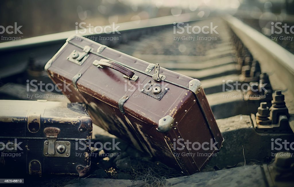 Old fashioned a suitcases on railroad tracks stock photo