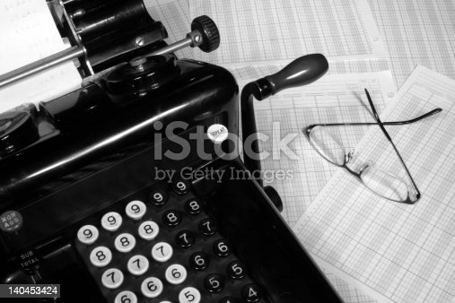This is an image of an old fashioned adding machine and ledger paper with glasses.