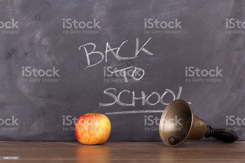 Old fashioned bell and apple against a blackboard foto royalty-free