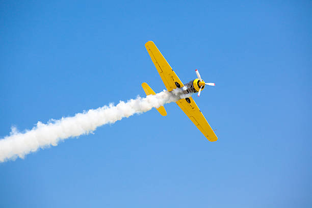 Old fashioned bright yellow propeller plane in sky stock photo
