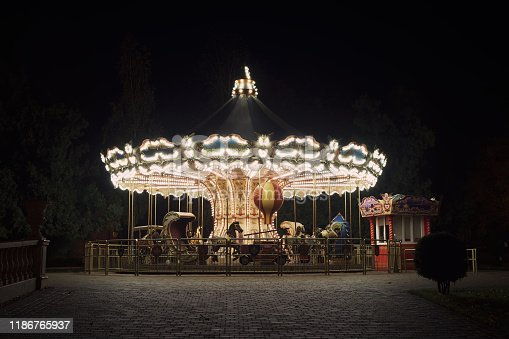 Old fashioned carousel backlit in a night park. Kharkov, Gorky Park.