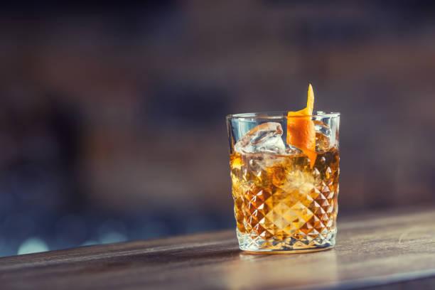 старомодный классический коктейльный напиток в хрустальном стакане на барной стойке - напиток стоковые фото и изображения