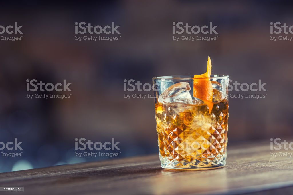 Old fashioned classic cocktail drink in crystal glass on bar counter stock photo