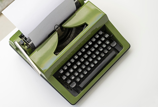 Old fashioned classic typewriter with sheet of paper on white wooden desk