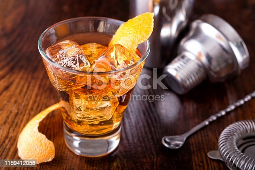 A delicious old fashioned cocktail on a wooden bar counter top.