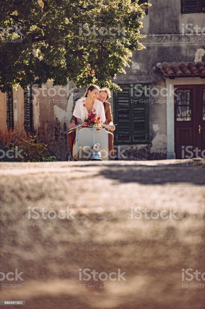 Old Fashioned Couple Riding Scooter On Village Street Stock
