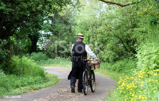 delivery man from the 1940's with wicker basket of bread on his vintage style bike, the model is wearing clothing from that time , straw boater and apron , model is pushing his bike up country lane