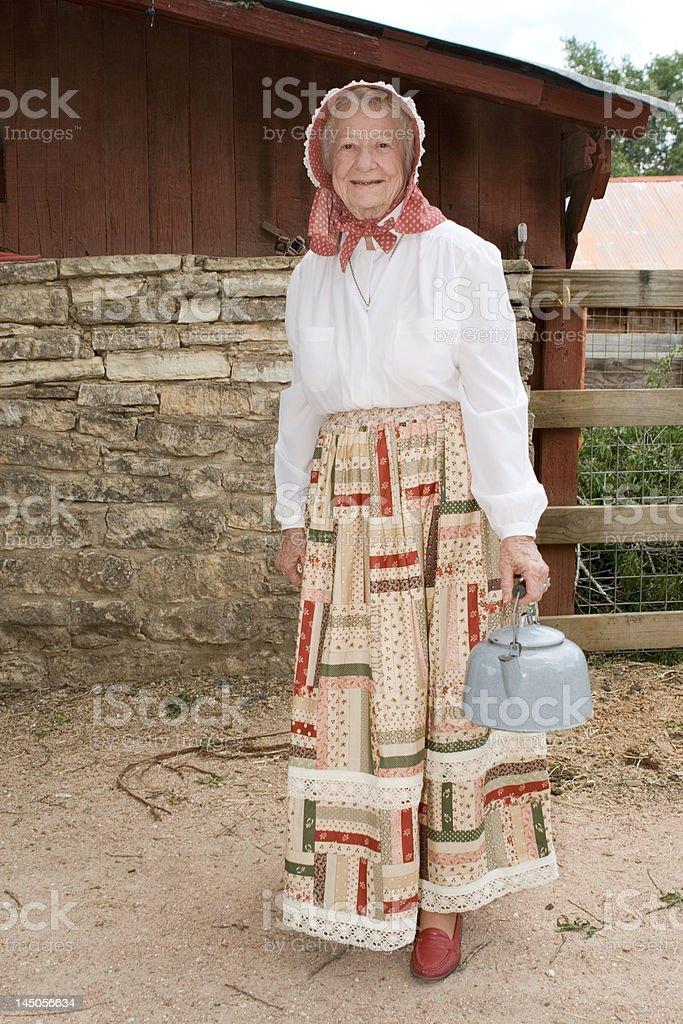 Old Fashioned Farm-woman Holding Tea Kettle in Farm Yard, History stock photo
