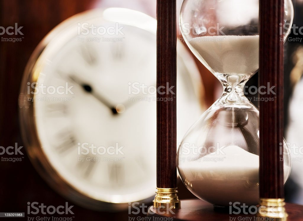 Old fashioned hourglass with clock dial in background royalty-free stock photo