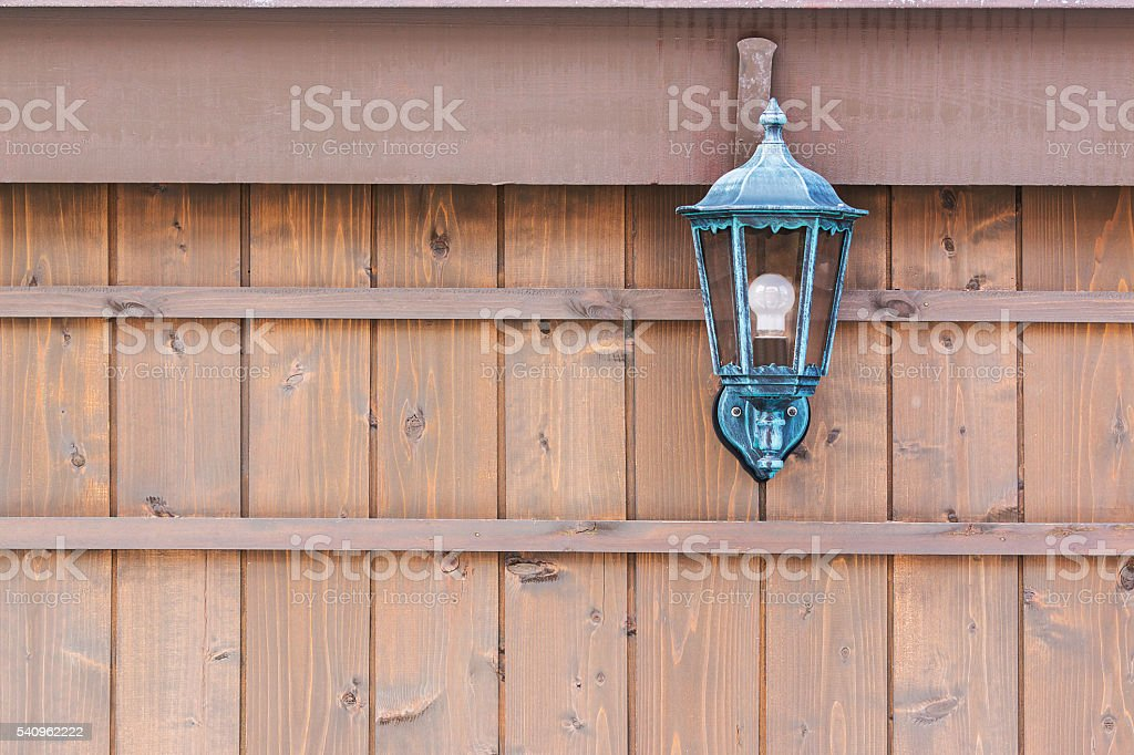 Old fashioned lantern on a brown wooden wall. stock photo