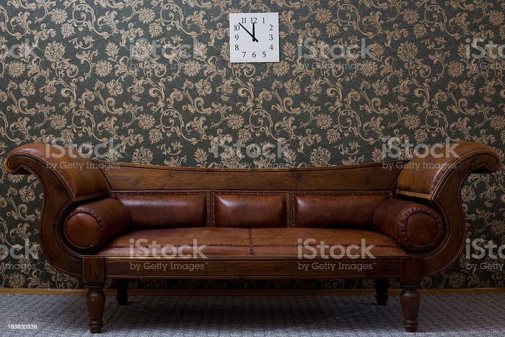 Old Fashioned Leather Sofa In Front Of Wallpaper Pattern Stock Photo ...