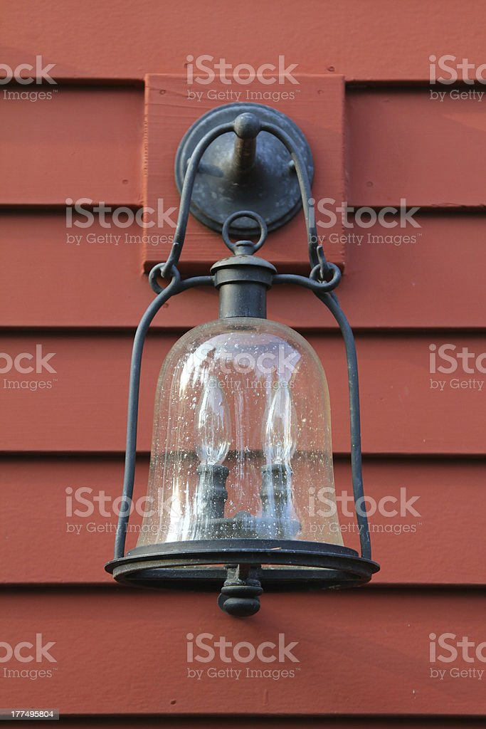Old fashioned light sconce on red exterior wall stock photo