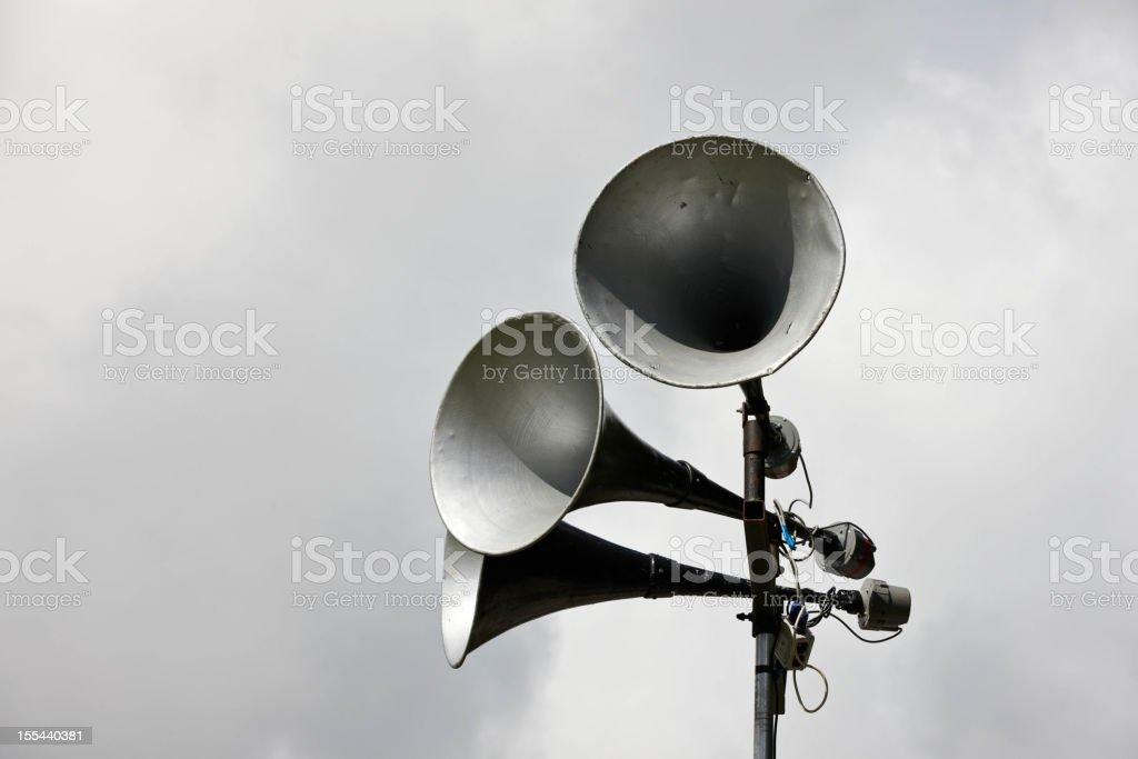 Old fashioned loudspeakers against grey skies stock photo