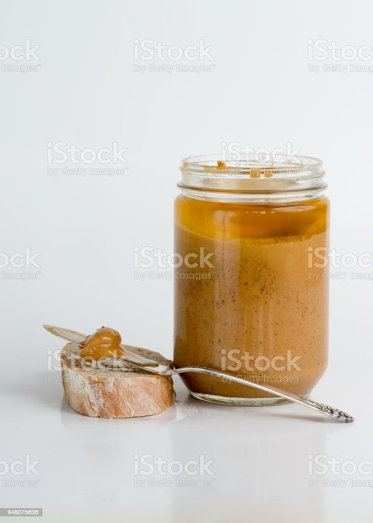 Old fashioned natural peanut butter in glass jar stock photo