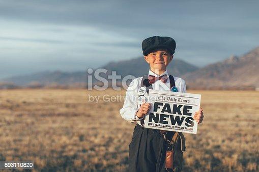 992091590 istock photo Old Fashioned News Boy Holding Fake Newspaper 893110820