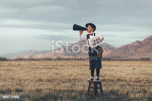 992091590 istock photo Old Fashioned News Boy Holding Fake Newspaper 893114566