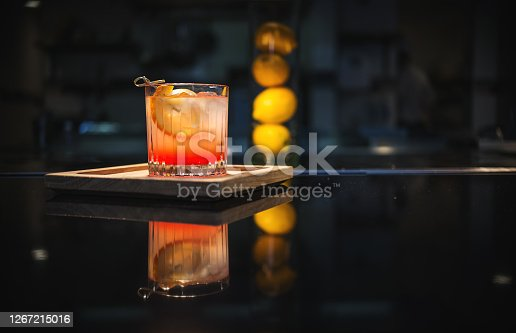 Old fashioned cocktail on the bar, on a wooden tray with lemons in the background. The Old Fashioned is a cocktail made by muddling sugar with bitters, then adding alcohol, such as whiskey or brandy, and a twist of citrus rind