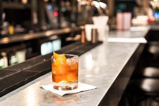 Old fashioned cocktail on the bar. The Old Fashioned is a cocktail made by muddling sugar with bitters, then adding alcohol, such as whiskey or brandy, and a twist of citrus rind.