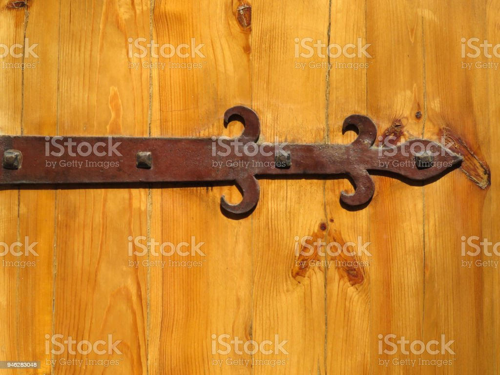 Old Fashioned Ornamental Metal Hinge Screwed To A Wooden Door   Stock Image  .