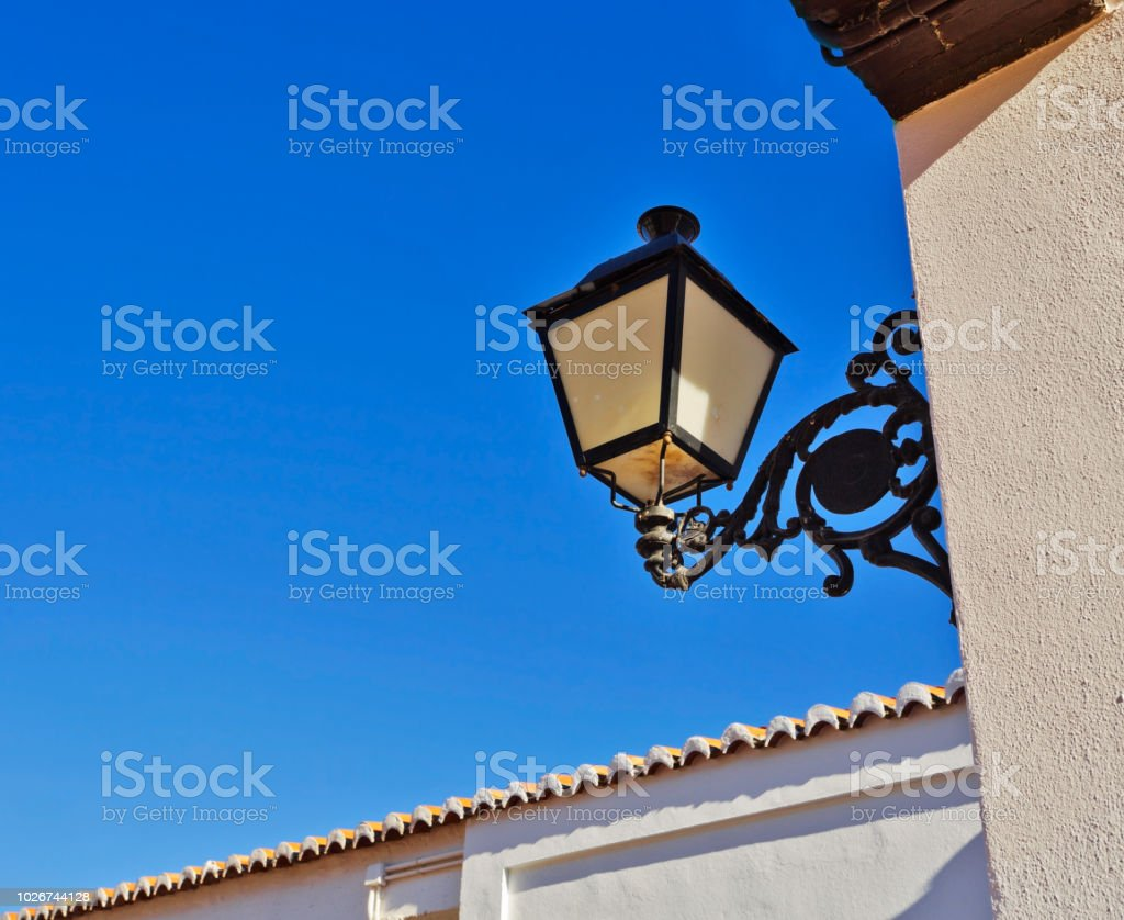 Оld fashioned outdoor lamp on white wall arhitecture detail. Mijas...